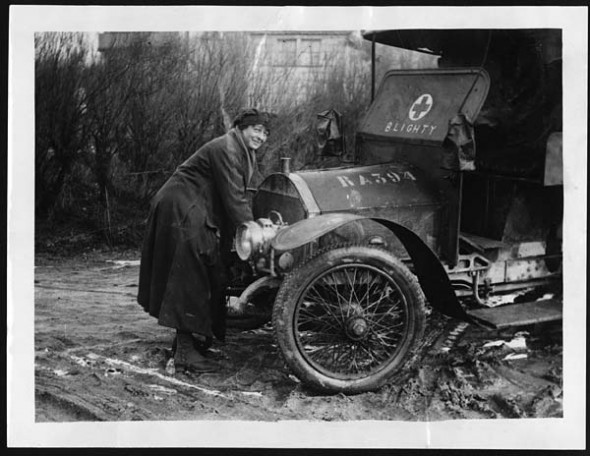 Driver of the First Aid Nursing Yeomanry cranking up an ambulance
