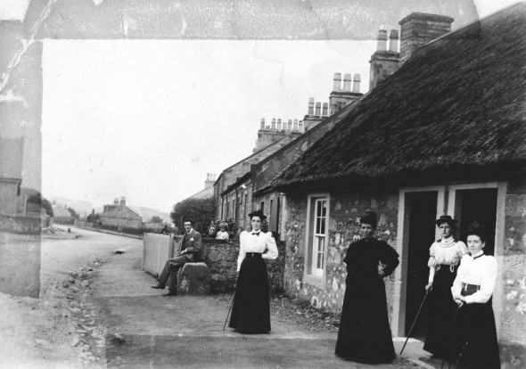 General view of people outside cottages at Troon, South Ayrshire, with thatched cottage in foreground, 1910
