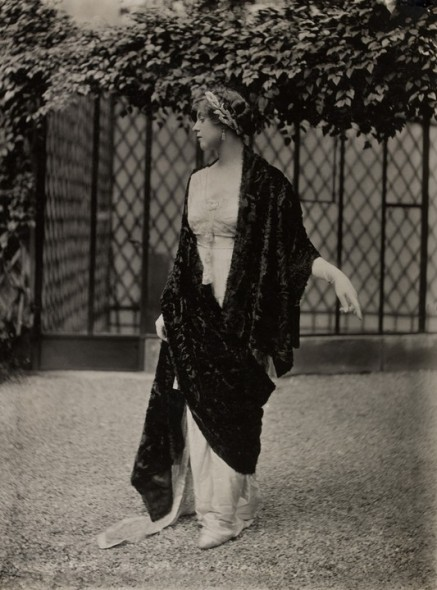 Model wearing a fur shawl over a chiffon dress and headband in the shape of a laurel crown.