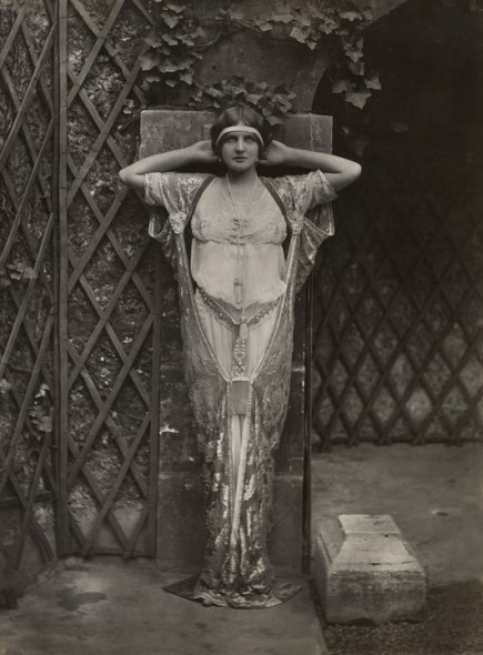 Model posing as a caryatid wearing embroidered tunic