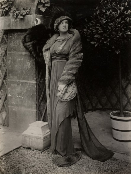 Model in fur coat and hat over a high-waisted dress