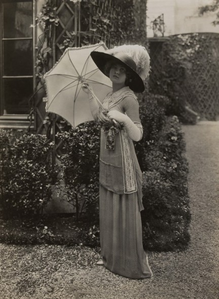 Model holding a parasol wearing a polka-dot cross-over dress
